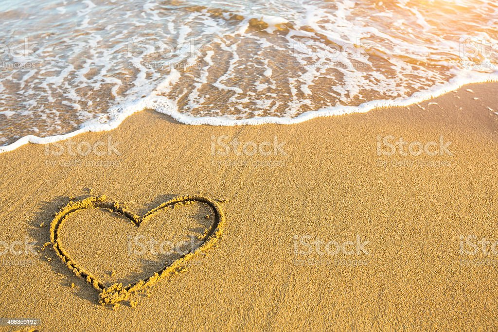Hand drawn heart on beach sand over soft gold sunset. royalty-free stock photo