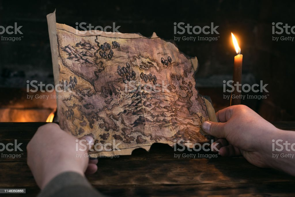 Adventurer man is holding in hands a treasure map over a burning fire...