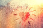 speech buble heart like sun on foggy window spattered with drops city, yellow red color, copyspace