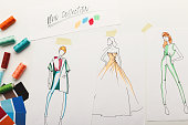 New fashion collection background. Hand drawn sketches of clothes on white board, color swatches and threads, top view. Creativity, dressmaking and design concept