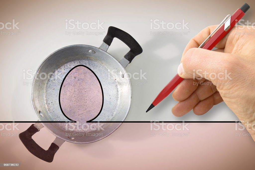 A hand draws the outline of a fried egg above an old aluminum pan - concept image stock photo