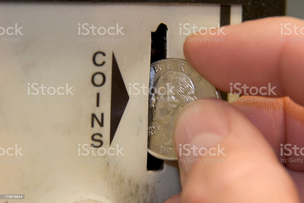 A hand dropping a quarter in to a coin slot stock photo