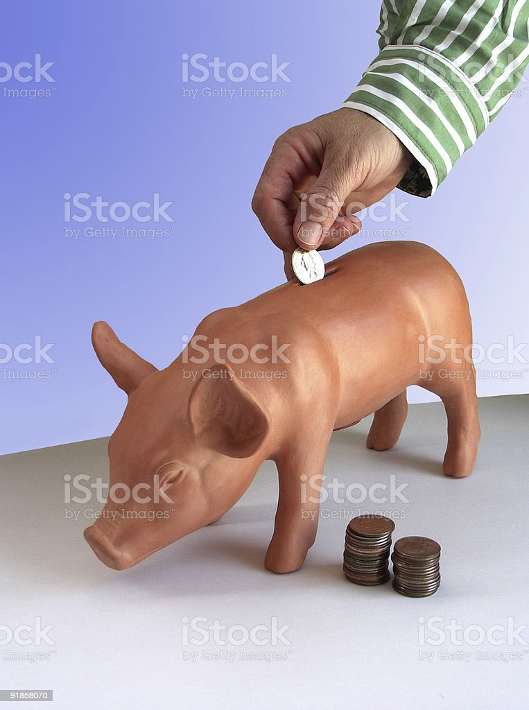 Hand dropping coin in piggy bank royalty-free stock photo
