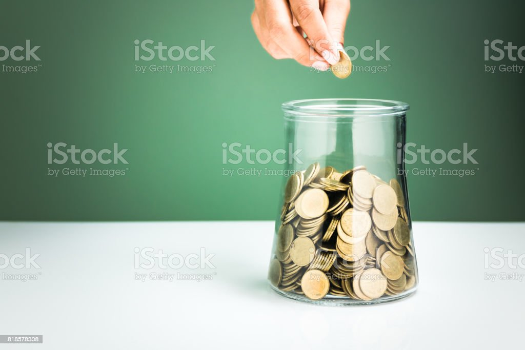hand drops money into a glass bottle ,savings concept stock photo