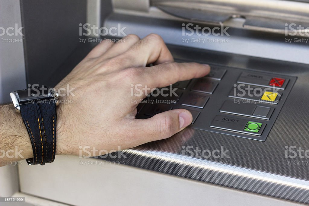 Hand entering personal identification number on ATM stock photo