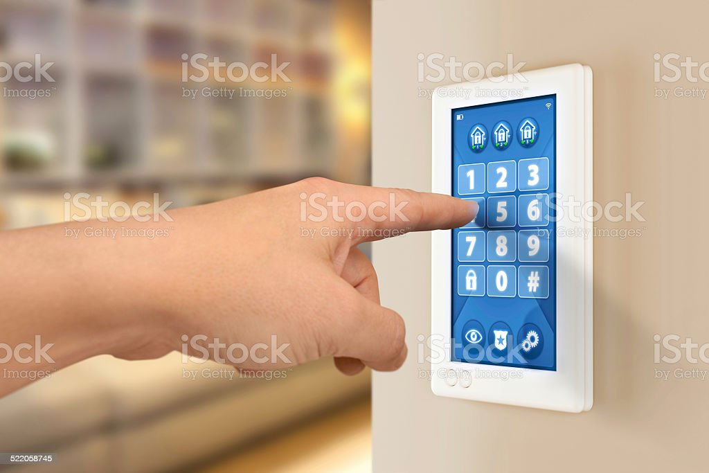 Hand entering pin code on home alarm security system stock photo