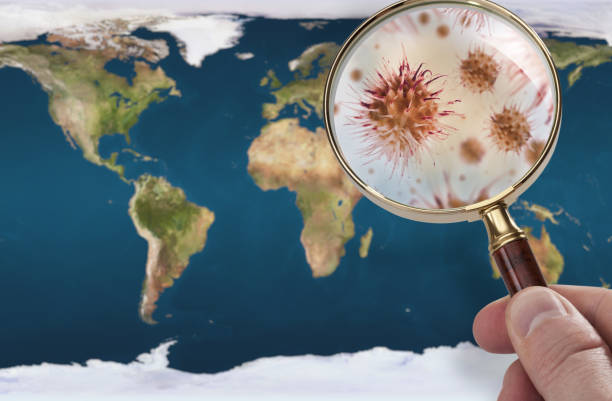 a hand examining the world with a magnifying glass and he sees a magnified virus. - aids healthcare foundation foto e immagini stock