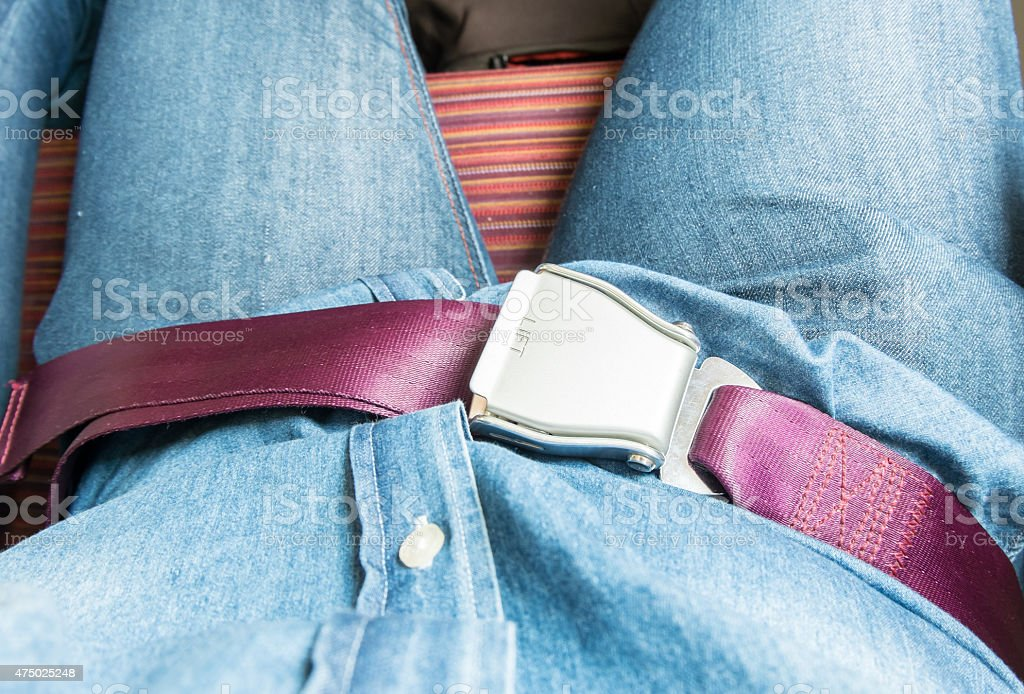 Hand fasten seat belt on airplane before take off. stock photo