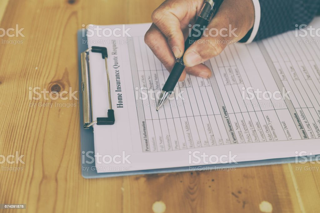 hand fill out home insurance form on a clipboard - real estate house protection concept royalty-free stock photo