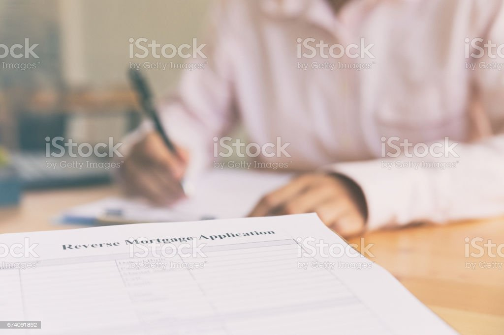hand fill out reverse mortgage loan application on a clipboard. A form to be filled by a homeowner who want to turn their asset into cash. stock photo