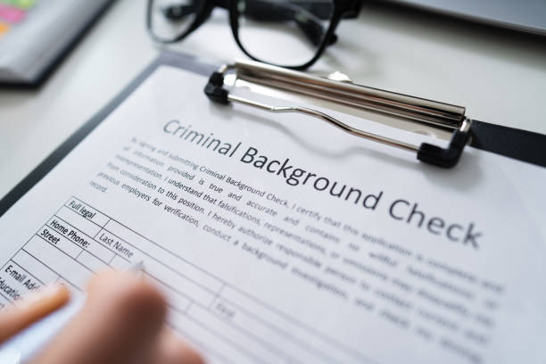 hand filling criminal background check application form - esaminare foto e immagini stock