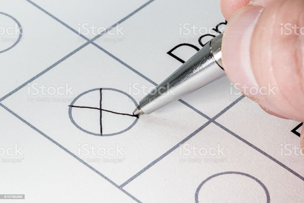 Hand filling out election form with silver pen stock photo