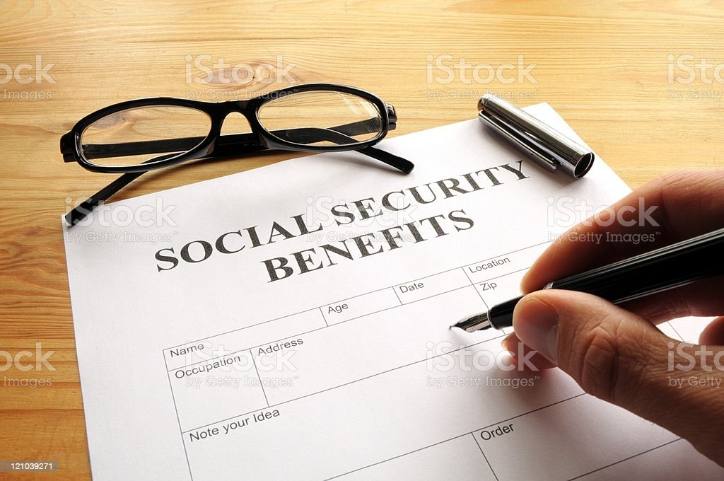 Hand filling out Social Security benefits paperwork stock photo