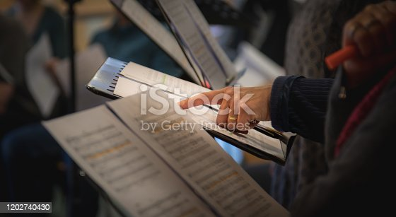 Hand points to notes during choir rehearsal, shallow depth of field