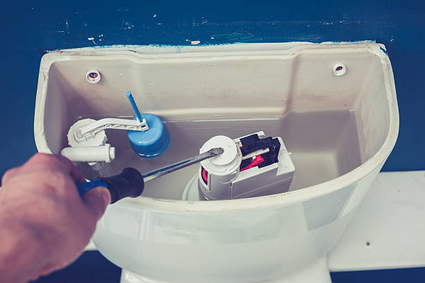 Hand fixing toilet Hand is fixing a toilet cistern at home flushing toilet stock pictures, royalty-free photos & images