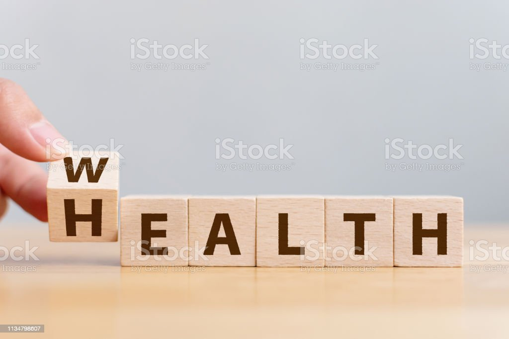 Hand flip wooden cube with word wealth to health. Investment in life insurance and healthcare concept royalty-free stock photo