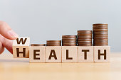 istock Hand flip wooden cube with word wealth to health with coins stack step up growing growth value. Investment in life insurance and healthcare concept 1142945282