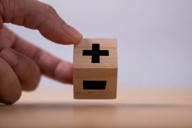 hand flipping black of plus to minus sign which print screen on wooden cube. - segno meno foto e immagini stock