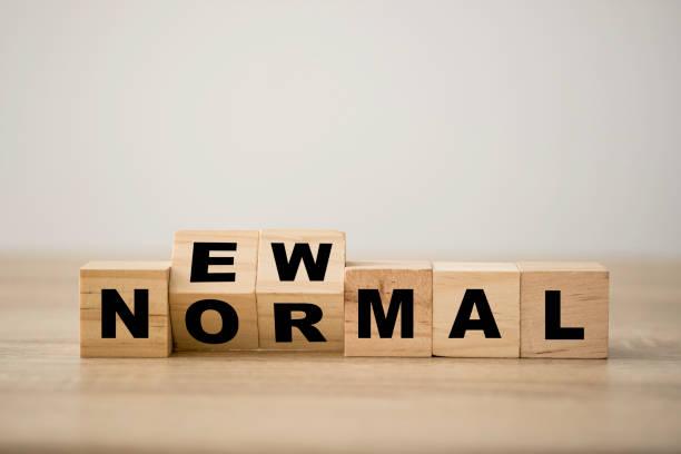 새로운 일반 문구에 대한 손 플립 나무 블록 큐브. 세계는 새로운 정상으로 균형을 변화 비즈니스, 경제, 환경 및 건강을 포함한다. - 일과 뉴스 사진 이미지