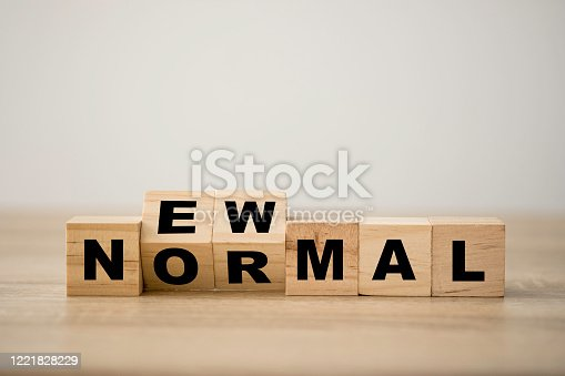 istock Hand flipping wooden block cubes for new normal wording. The world is changing to balance it into new normal include business , economy , environment and health. 1221828229
