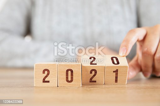 Female hand changing year 2020 to 2021 with wood cubes