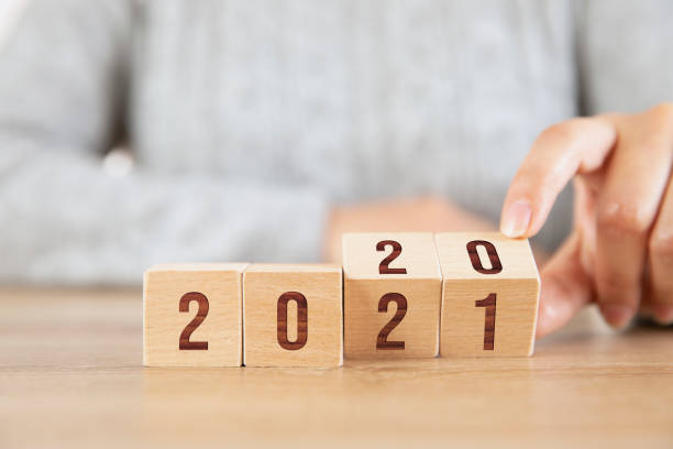 Hand Flipping Wooden Cubes from Year 2020 to 2021 stock photo