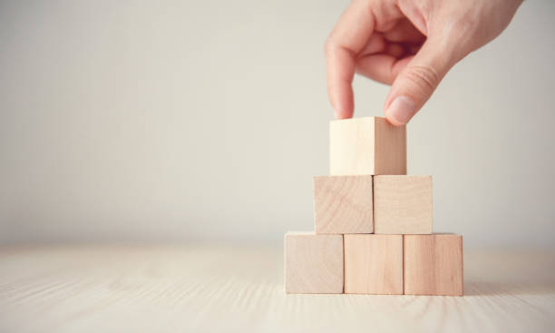 Hand flips blank wood cube block on top pyramid, for create icon symbol to success concept. stock photo