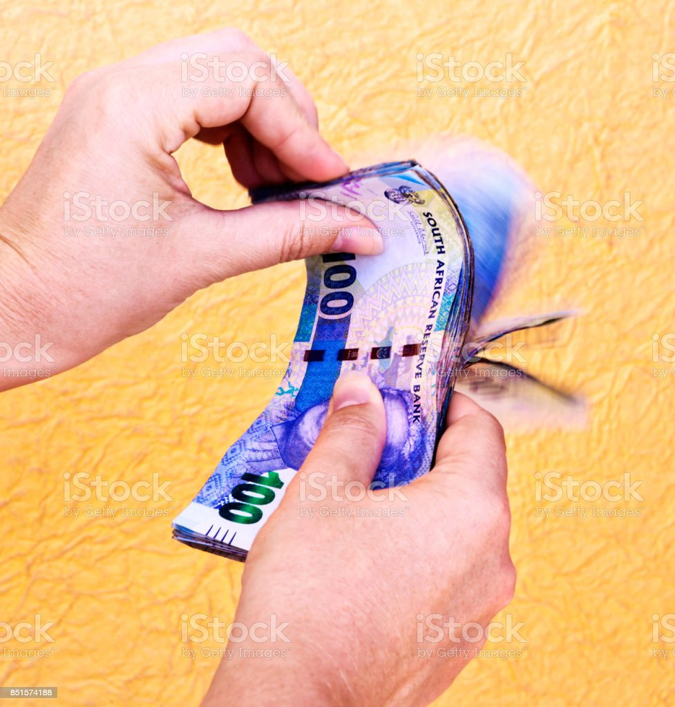 Hand flips fistful of One Hundred Rand banknotes at speed stock photo