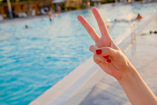 hand forming peace sign on blurred swiming pool - bester nagellack stock-fotos und bilder
