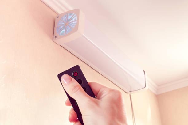 방 안의 공기를 쿼트하기 위한 살균 공기 재순환기를 원격 제어로 제어할 수 있습니다. - 자외선 차단 뉴스 사진 이미지