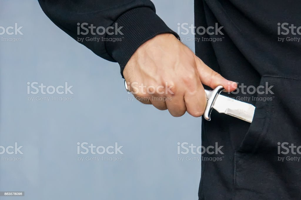 Hand from the pocket of the black jacket pulls out a folding knife close up. stock photo