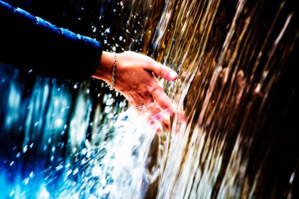 hand wird im bergbach nass. - armband water stock-fotos und bilder