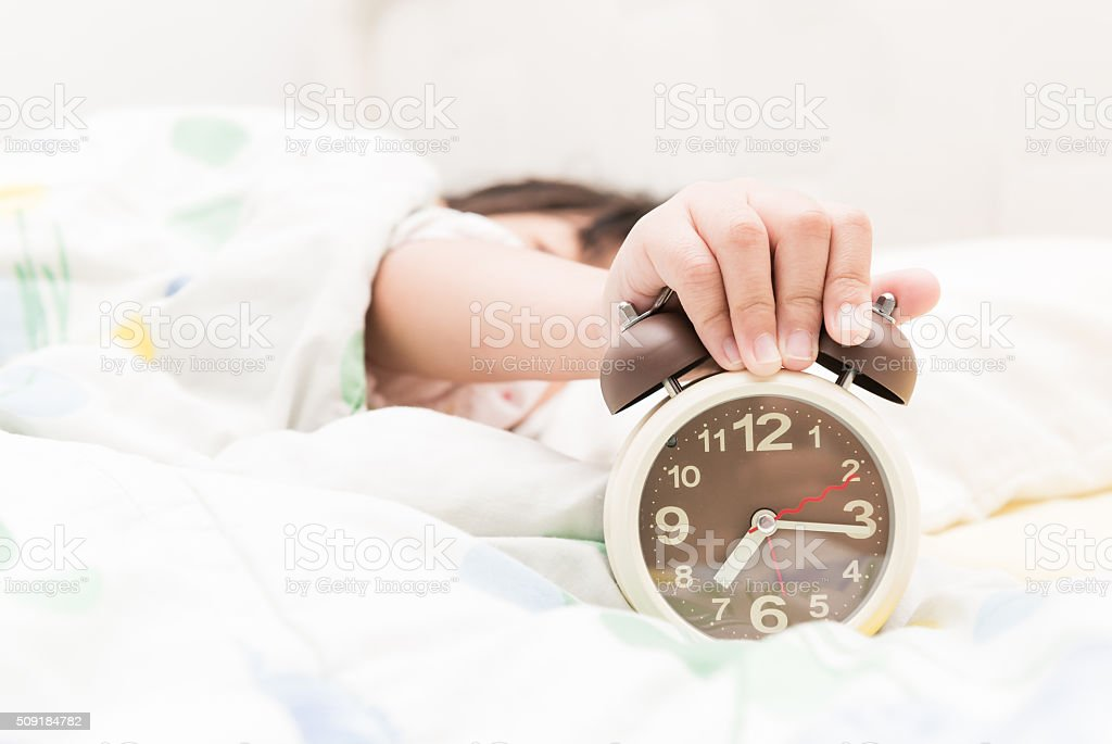 Hand girl reaching out for alarm clock stock photo