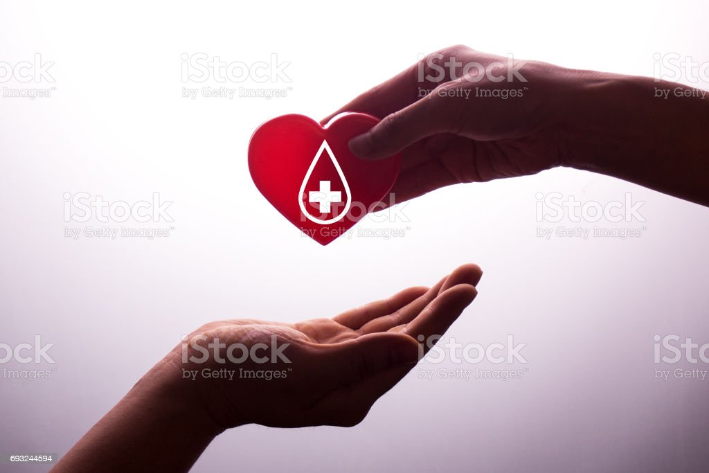 A hand gives a red heart to a hand - blood donation,world blood donor day stock photo