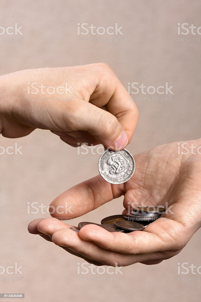 hand giving a coin to another person stock photo