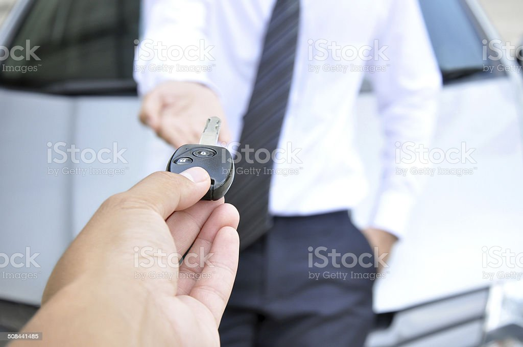 Hand giving car key - car sale & rental service stock photo
