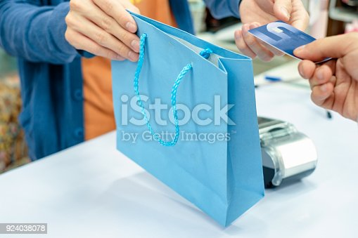 914593772istockphoto Hand giving credit card and take paper bag from staff cashier in store 924038078