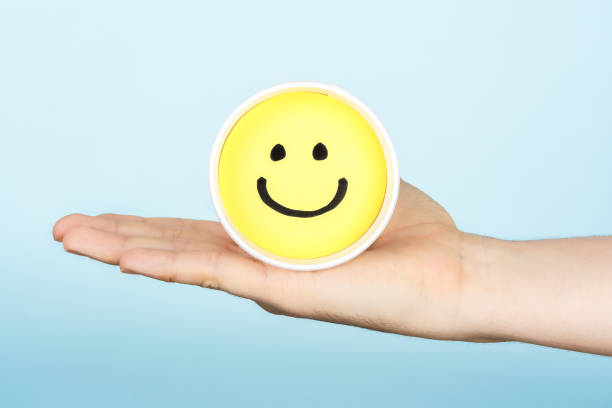 Hand giving hapiness concept. Yellow happy face emoticon. stock photo