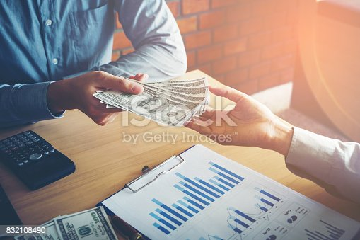 istock Hand giving money United States Dollars bills ,Hand receiving money from businessman 832108490