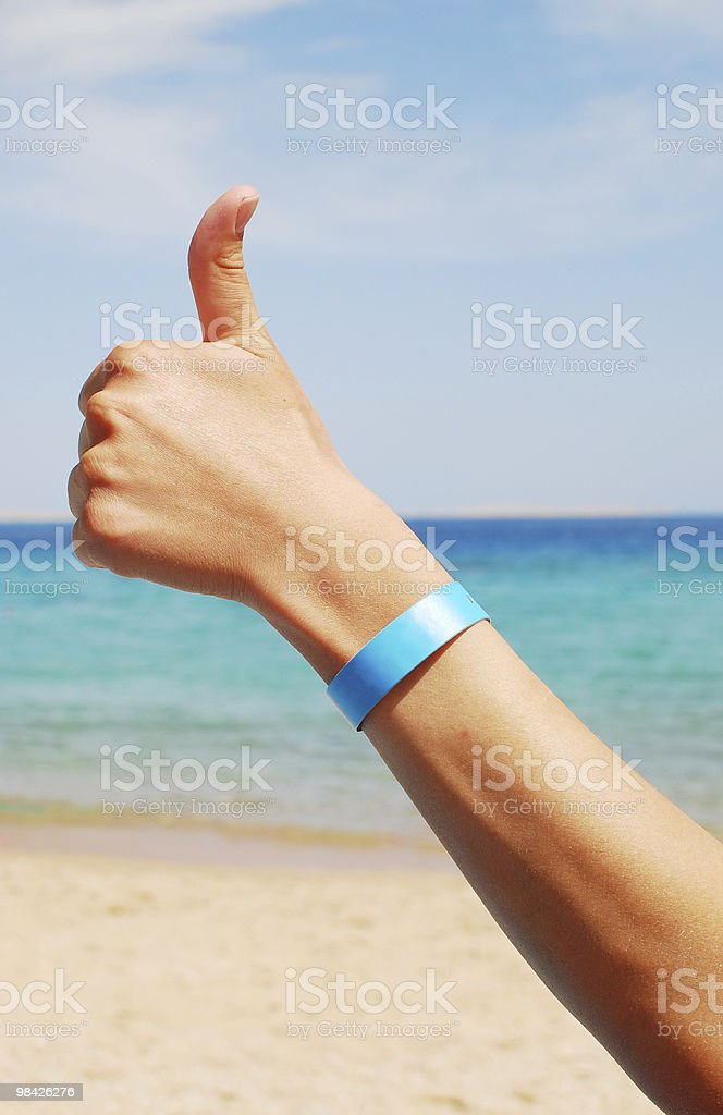 A hand giving the thumbs up with blue band on wrist royalty-free stock photo
