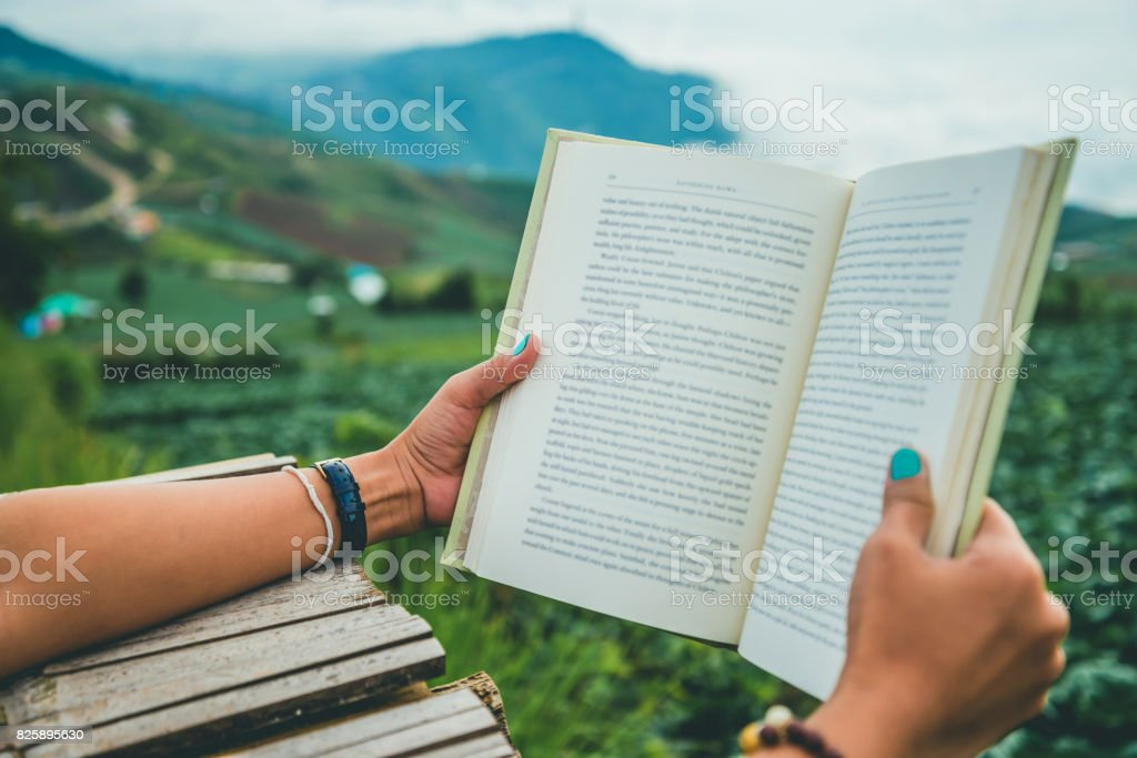 Hand grab women reading books. Morning atmosphere The mountains are foggy. phetchabun phutubberg thailand stock photo