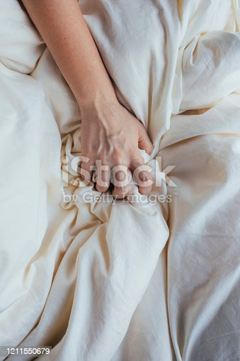 Close up of a woman's hand grabbing a bed sheet.