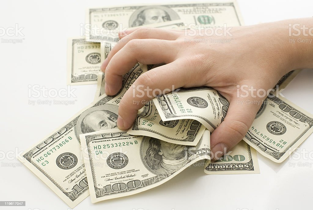 A hand grabbing from a pile of $100 bills stock photo
