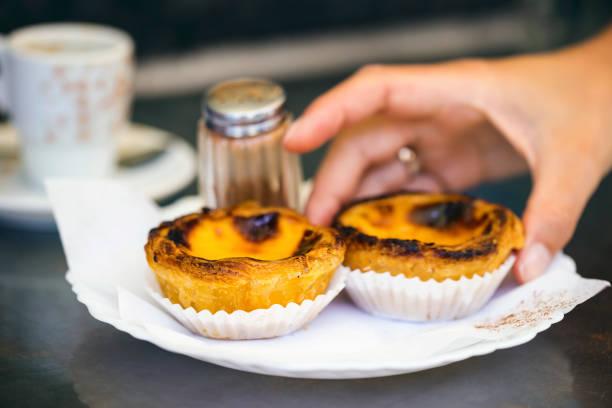 hand greifen typisch portugiesischen gebäck - pastel de nata. - portugiesische desserts stock-fotos und bilder