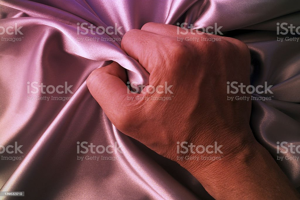 A hand grasps pink silk sheets stock photo
