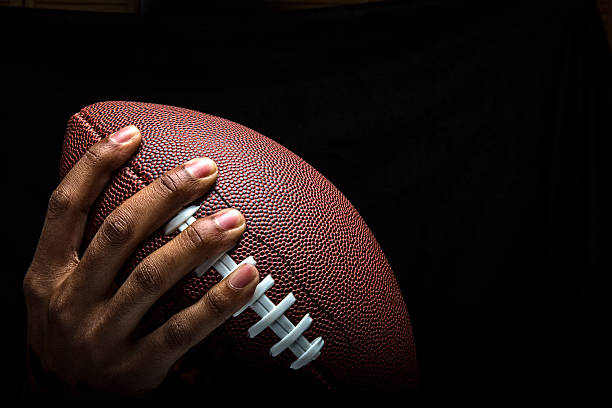 Hand Gripping Football to Pass stock photo