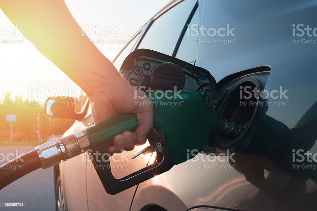 hand guiding the fuel in the car stock photo