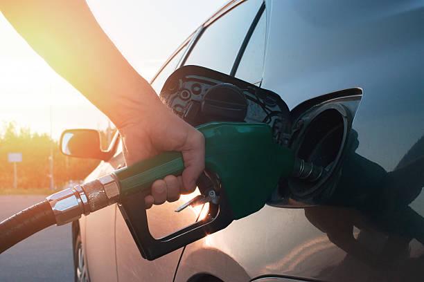 hand guiding the fuel in the car - echar combustible fotografías e imágenes de stock