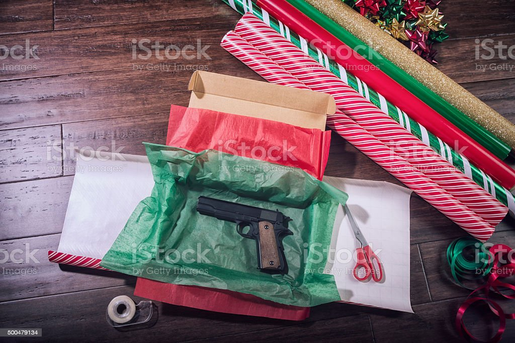 Hand gun being wrapped for Christmas stock photo