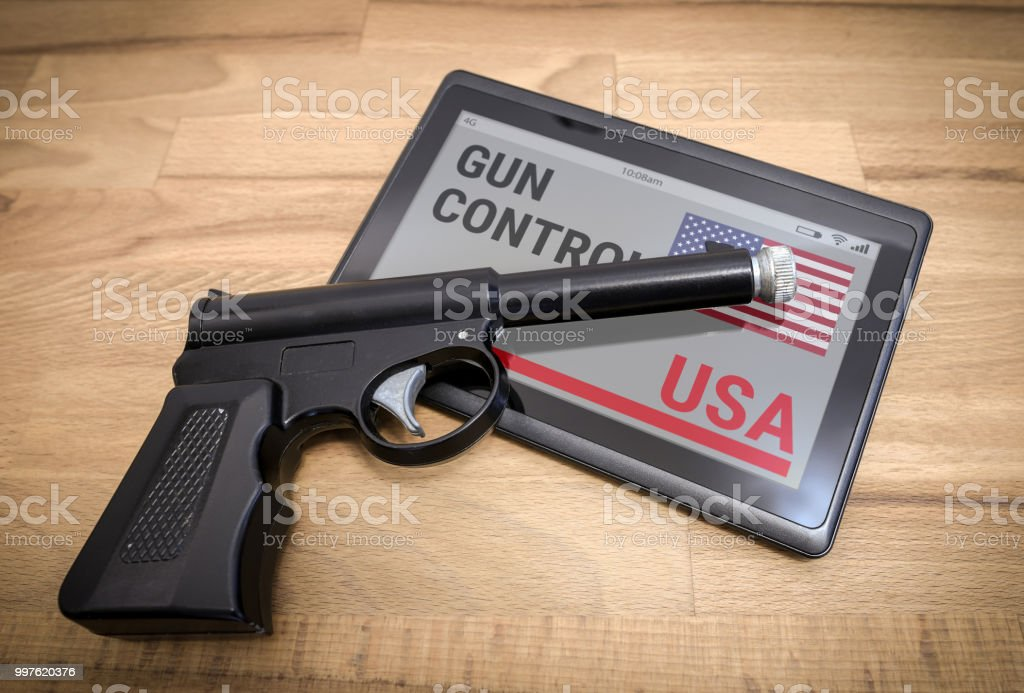 Hand gun on a tablet device with 'Gun Control USA' stock photo